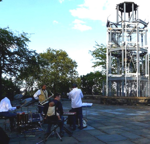 The Craig Harris band performing on the Acropolis with the Harlem Fire Watchtower in the background.