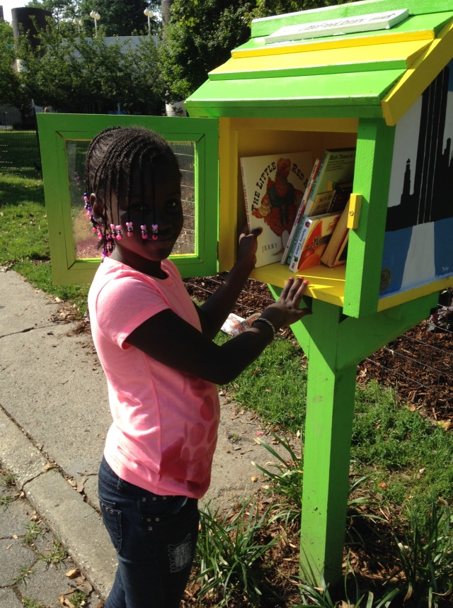 Little Girl in silhouette selecting a book from the Little Free Library