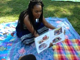 MGPAlliance Dedicated member and Reading Circle Committee Member Reading to kids on Lawn A.